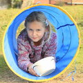 Girl eating in blue kids tunnel little lying and from bowl for Stock Photos