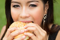 Girl eating a cheeseburger teenage in the park Royalty Free Stock Images