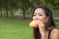 Girl eating a cheeseburger teenage in the park Stock Photography