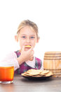 Girl eating cookies with honey on a white background isolated sitting at wooden table Royalty Free Stock Photos