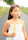 Girl eating corn little with pink sun glasses in white t shirt Royalty Free Stock Photography