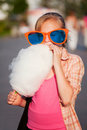 Happy teen girl in sunglasses eating cotton candy walking in city street Royalty Free Stock Photo