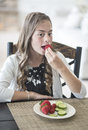 Girl eating a delicious healthy plate of strawberries and cucumbers Royalty Free Stock Photo