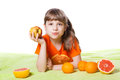 Girl eating fruit on a green background Stock Photos