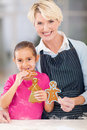 Girl eating gingerbread cookie beautiful little her grandma just baked Royalty Free Stock Images