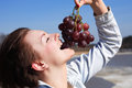 Girl eating grapes beautiful young red outdoor on blue sky background Stock Images