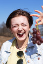 Girl eating grapes beautiful young red outdoor on blue sky background Stock Photo