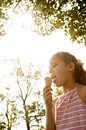 Girl eating ice cream in park portrait of a young an the under golden light and trees Royalty Free Stock Image