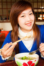 Girl eating meatball with shopstick and spoon Stock Photo