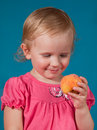 Girl eating a peach little Stock Image