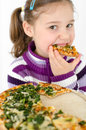 Girl eating pizza eats a with spinach Royalty Free Stock Photos
