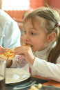 Little girl eating pizza and soup