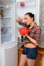 Girl eating soup from pan near an open refrigerator with a pot of the at night Royalty Free Stock Photo