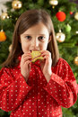 Girl Eating Star Shaped Cookie In Front Of Tree Royalty Free Stock Images