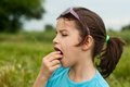 Girl eating a strawberry little that is Royalty Free Stock Photo