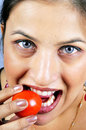 Girl eating tomato Stock Images