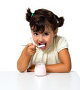 Girl eating yogurt isolated on white Stock Photography