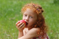 Girl eats apple on lawn in green summer park, close up, s