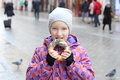 The girl eats a bagel with poppy on a city street, cold day. Royalty Free Stock Photo
