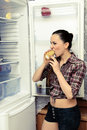 The girl eats cake near the refrigerator before bed Royalty Free Stock Photo