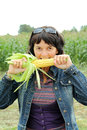 Girl eats a corn on a meadow Royalty Free Stock Image