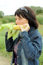 Girl eats a corn on a meadow Stock Image