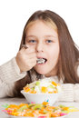 Girl eats fruit dessert spoon while sitting at a table little on white background isolated Royalty Free Stock Images