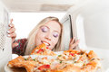Girl eats pizza out of the microwave Stock Images