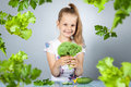 Girl eats vegetables and herbs Royalty Free Stock Photography
