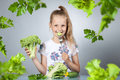 Girl eats vegetables and herbs Stock Image