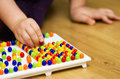 Girl with educational pin puzzle toy closeup of a little hand playing colorful game at home sitting on hardwood floor Royalty Free Stock Image