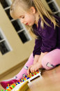 Girl with educational pin puzzle toy a cute little playing colorful game at home sitting on hardwood floor Stock Photos