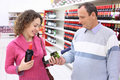 Girl and elderly man in shop with wine bottles Stock Image