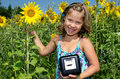 Girl with electricity meter in sunflower field happy standing a current Royalty Free Stock Photography