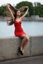 Girl on the embankment happy with red dress sitting parapet of of river and expand hair Stock Photo