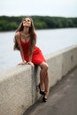 Girl on the embankment happy with red dress sitting parapet of of river and looks up Royalty Free Stock Images