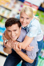 Girl embraces man in the shop men concept of happy relationship and affection Royalty Free Stock Images