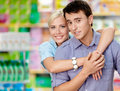 Girl embraces man in the shopping center men concept of happy relationship and affection Royalty Free Stock Images