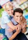 Girl embraces man in the shopping mall men concept of happy relationship and affection Royalty Free Stock Photos