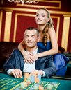 Girl embracing gambler at the playing table Stock Photos