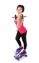 The girl is engaged in fitness with dumbbells on stepper a white background Royalty Free Stock Photography