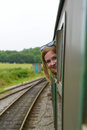 Girl enjoy travel by train looking outside the window of a wagon and to Stock Images