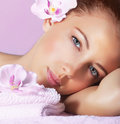 Girl enjoying dayspa image of cute young lady closeup portrait of pretty woman with orchid flower in head on pink background Stock Photos