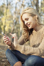 Girl enjoying internet wireless on smartphone in n a modern young woman outside a forest glade having fun using Royalty Free Stock Image