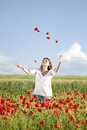 Girl enjoying summer in a poppy field young casual woman relaxing Royalty Free Stock Photography