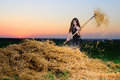 The girl in an evening dress with a pitchfork near a haystack at sunset at Royalty Free Stock Images