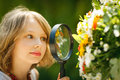 Girl exploring flowers through the magnifying glass outdoors Stock Photography