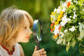 Girl exploring flowers through the magnifying glass outdoors Stock Image
