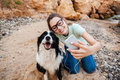 Girl in eyeglasses taking selfie with her dog on smartphone Royalty Free Stock Photo