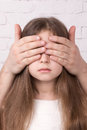 Girl with eyes closed strange hands portrait of serious child closing her Royalty Free Stock Photo